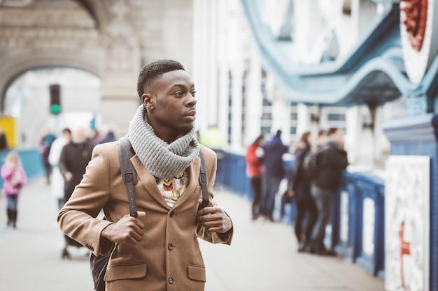 タワーブリッジの上を歩くロンドンの若い黒人男性 Premium写真