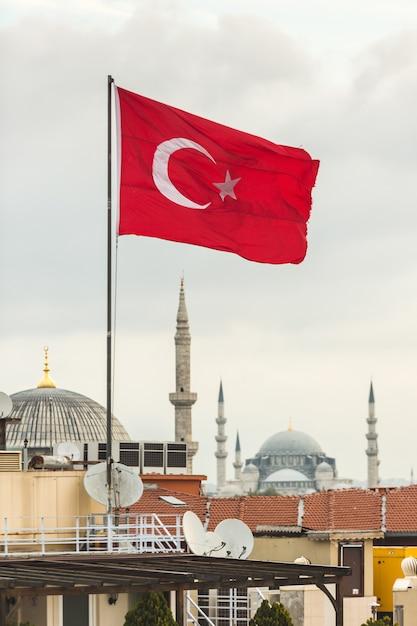 トルコの国旗とイスタンブールの街並みとモスク Premium写真
