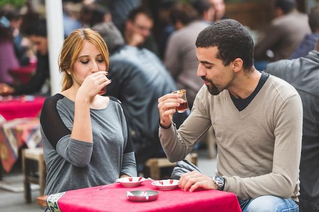 トルコのカップル、イスタンブールのケイ、伝統的なお茶を飲む Premium写真