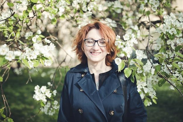 Женщина улыбается под цветущим деревом Premium Фотографии