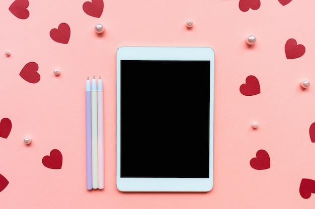 Красные бумажные украшения конфетти сердца, белый жемчуг, ручки и таблетки на розовом фоне. Premium Фотографии
