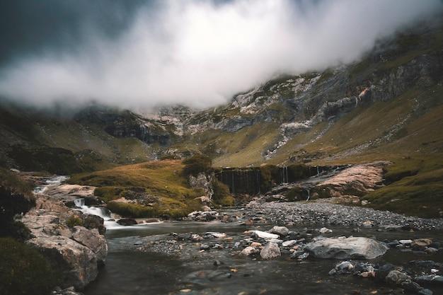 川が下がり、嵐が降り注ぐ曇りの風景。 Premium写真