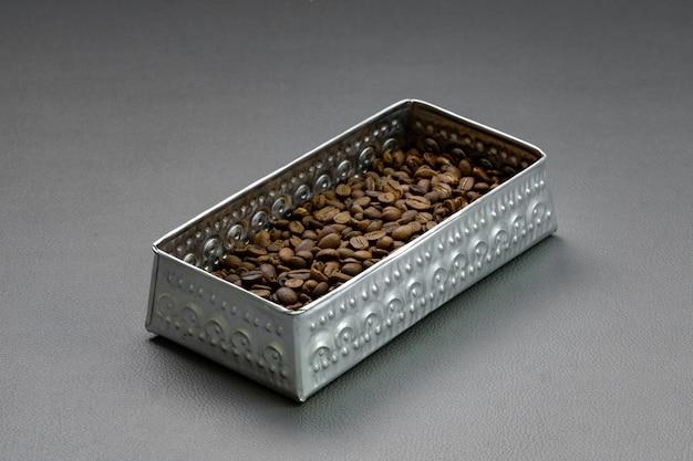 Обжаренные кофейные зерна помещают в алюминиевые коробки-контейнеры на серой основе. Premium Фотографии