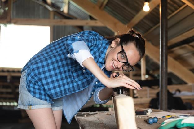 木の板の正面に平面を働く安全メガネの女 Premium写真