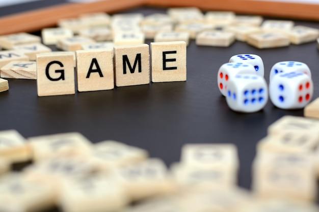 サイコロと円の中の文字と黒のボード上の木製の文字で単語ゲーム Premium写真
