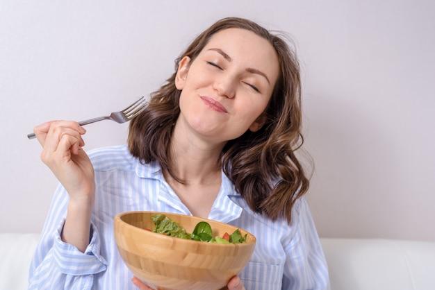 喜びと目を閉じて健康的な野菜のサラダを食べる青いシャツを着た女性のクローズアップ Premium写真