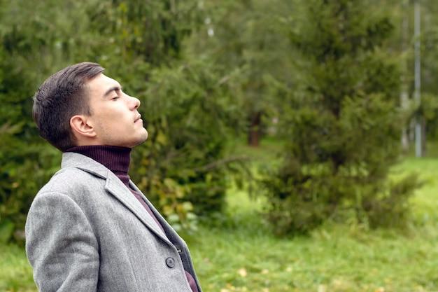 公園の新鮮な秋の空気で呼吸している灰色のコートを持つ魅力的な若者の肖像 Premium写真