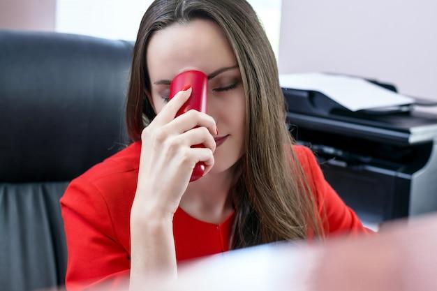 頭痛に苦しんで手に赤いスーツと赤い電話で暗い髪の魅力的なビジネス女性。オフィスでの勤勉の概念。モノクロ Premium写真
