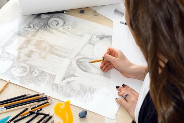 Руки студента-архитектора с карандашом готовят узор из света и тени, дизайн балясины крупным планом на деревянном столе Premium Фотографии