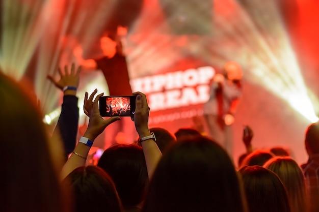 コンサートでスマートフォンを持つ手のシルエット Premium写真