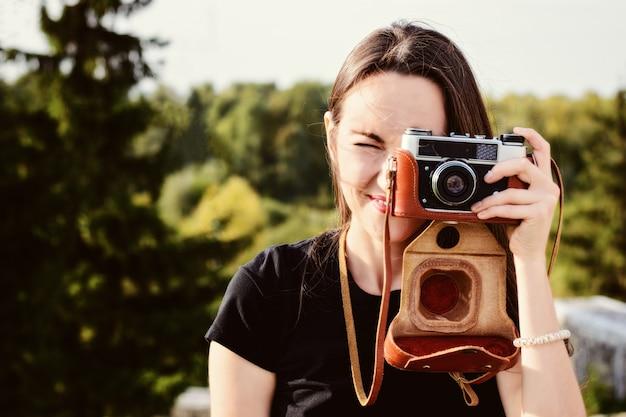 若い幸せな女性写真家は、レトロなカメラで公園を散歩します Premium写真