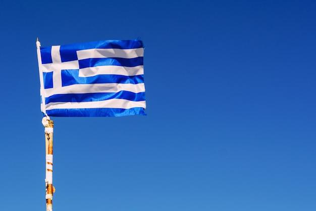 青い空を背景に風になびく小さなギリシャの旗 Premium写真
