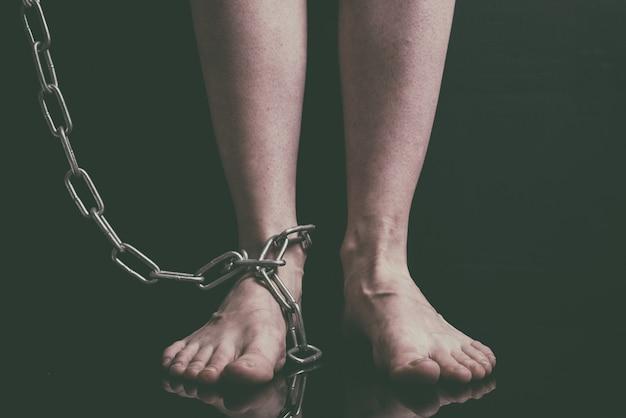 白人女性の足は床に金属チェーンのチェーンをクローズアップ Premium写真
