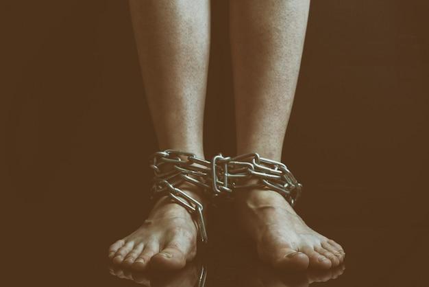 Грязные женские ноги с распухшими венами висят связанные металлические цепи крупным планом Premium Фотографии