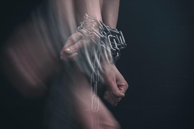 女性の手が鎖でつながれ、動き出す Premium写真