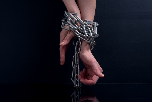 吊り下げられた金属チェーンに関連する腫れた静脈で疲れた女性の手 Premium写真