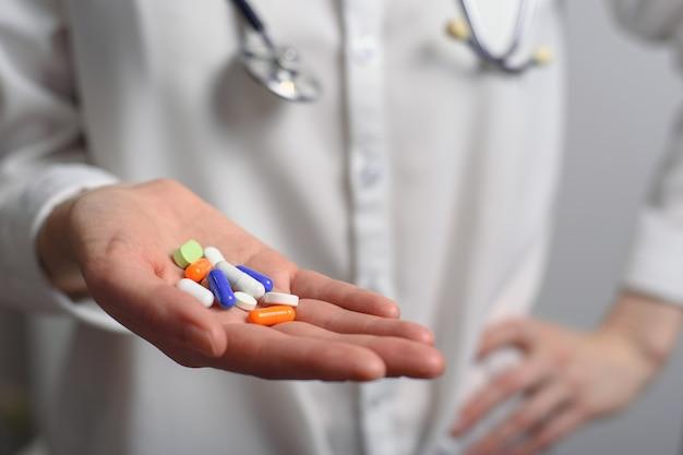 Разноцветные таблетки от ладони доктора-женщины со стетоскопом на шее Premium Фотографии