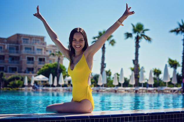 バカンスプールの端に黄色の水着に座って彼女の手で幸せな笑顔の女の子 Premium写真