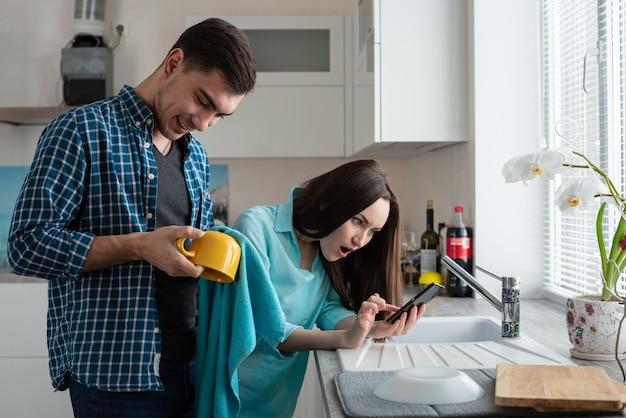 若い家族。男性が黄色いカップをこすり、女性が電話を見てショックを受けた、予想外のニュース Premium写真