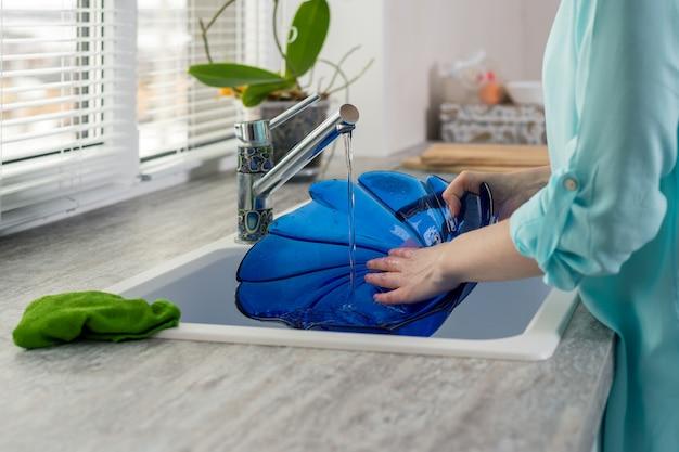 女性の手のクローズアップは、窓の前の台所の流しの水の圧力の下で青いプレートをすすぎます Premium写真