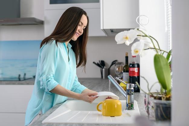 柔らかな光の窓の前でお皿を洗う若い女性 Premium写真