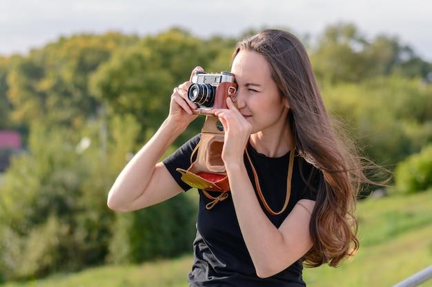 街でレトロなカメラで写真を作る幸せなブルネットの女性 Premium写真
