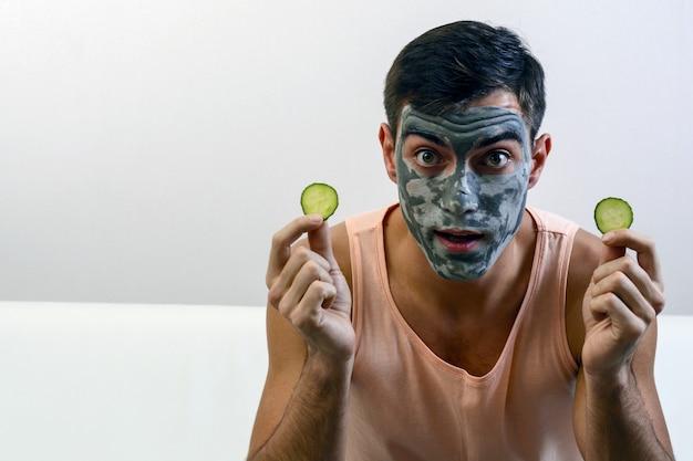 Эмоциональный портрет человека в глиняной маске на лице с огурцами в руках. Premium Фотографии