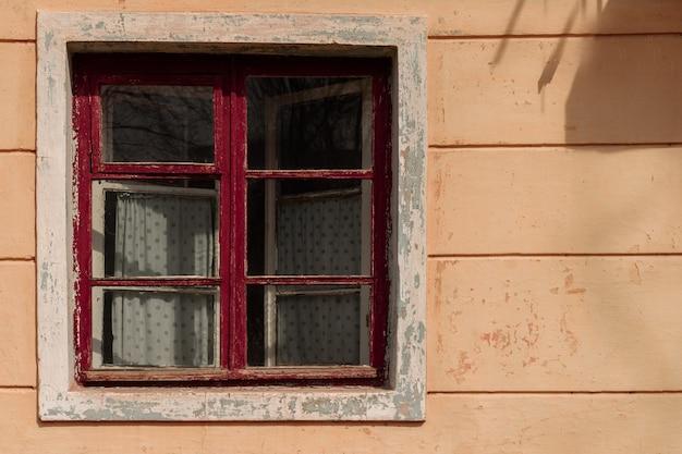 木製の赤いフレームとカーテンと廃屋で古い窓 Premium写真