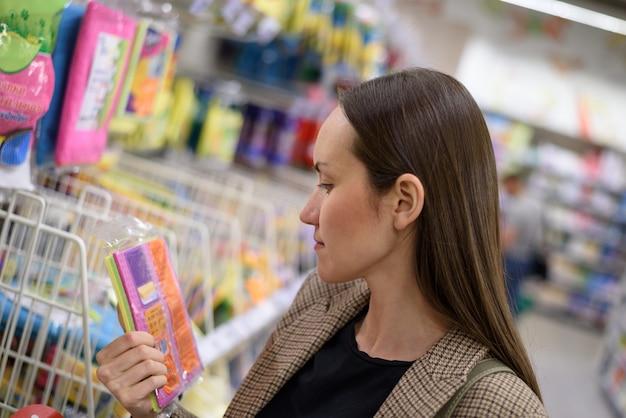 スーパーマーケットのジャケットの若いビジネス女性がキッチンぼろを選択します Premium写真