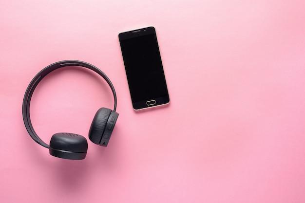 音楽愛好家のためのガジェットの概念。ワイヤレスヘッドフォンとスマートフォン Premium写真
