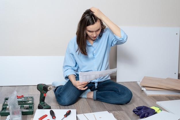 家具を組み立てるための指示を持つ青いシャツを着た思いやりのある女性が床に座っています。 Premium写真