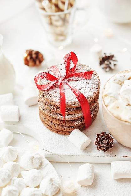 Рождественское печенье и зефир на белом у окна Premium Фотографии