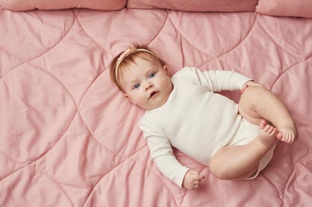 Девочка четырех месяцев лежит на розовой стене Premium Фотографии