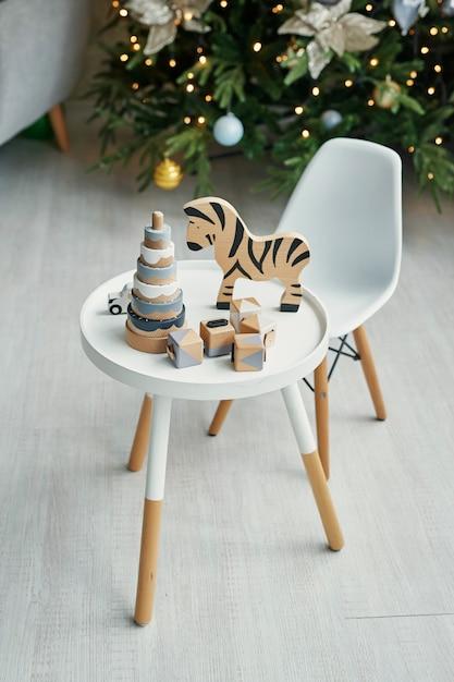 スカンジナビアの子供用家具。クリスマスツリー、テーブル、椅子、木製の教育玩具を備えた北欧の子供部屋。ロフトスタイルの子供部屋のインテリア。 Premium写真
