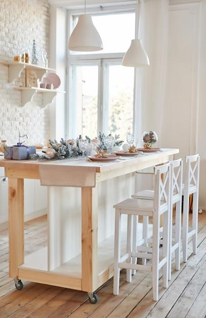 Внутренняя светлая кухня с рождественским декором и деревом. белая кухня в классическом стиле. рождество на кухне. яркая кухня в белых тонах с рождеством. Premium Фотографии