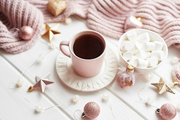 クリスマスの装飾、ボール、ウィンドウのウールチェック柄、家の快適さの概念、季節ごとの冬のお祝い。 。マシュマロとクリスマスピンクカップ。 Premium写真