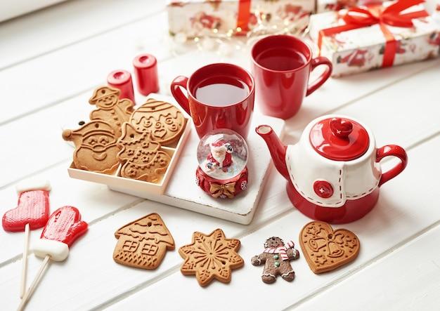 Рождественское печенье и кружка горячего чая, рождество. рождественские пряники, конфеты, кофе в красной чашке на деревянный стол на столе морозный зимний день окна. домашний уютный отдых. шаблон открытки Premium Фотографии