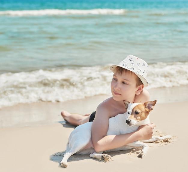 ビーチで犬ジャックラッセルを持つ少年 Premium写真