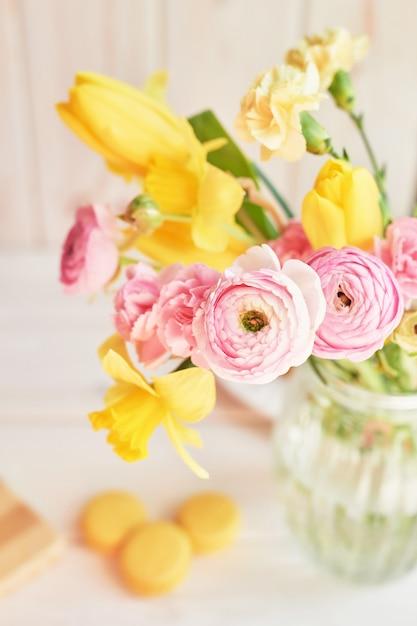 春の花の花束:チューリップ、カーネーション、ラナンキュリー、水仙の花瓶のテーブルの上。母の日挨拶 Premium写真
