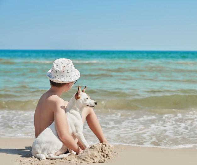 Мальчик с собакой джек рассел на пляже Premium Фотографии