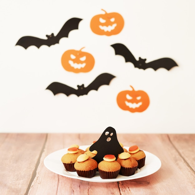 ハロウィーンは、カボチャとコウモリを背景にテーブルの上のカップケーキを扱います Premium写真