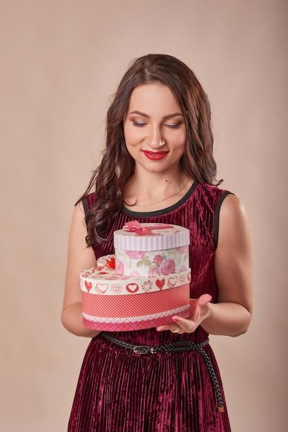 ギフト用の箱を保持している赤いドレスの陽気な女性の肖像画 Premium写真