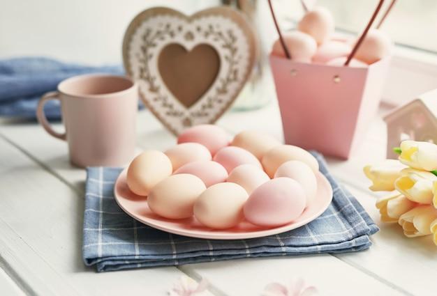 Пасхальная композиция с желтыми тюльпанами и розовыми яйцами Premium Фотографии