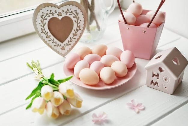 Весенняя композиция с желтыми цветами тюльпана, розовыми яйцами, рамкой в форме сердца и крошечным деревянным домиком Premium Фотографии