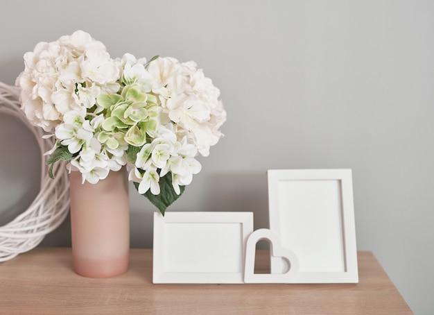 白い花の花束とテーブルの上の素敵な白いフォトフレーム Premium写真