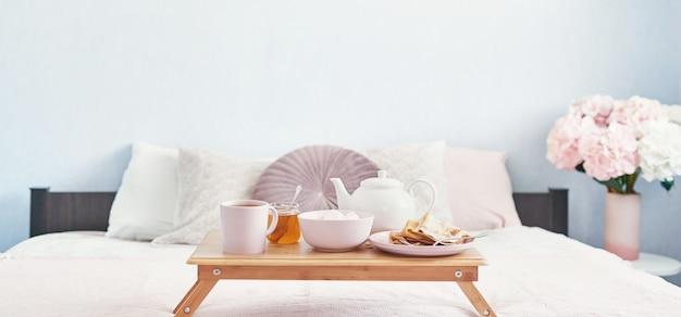 ホテルの部屋でベッドで朝食。宿泊施設。ベッドの上のトレイにパンケーキとティーカップとベッドで朝食します。 Premium写真