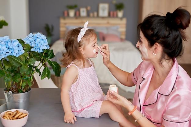 家族の母と朝の赤ん坊の娘は、キッチンで朝食をとります。 Premium写真
