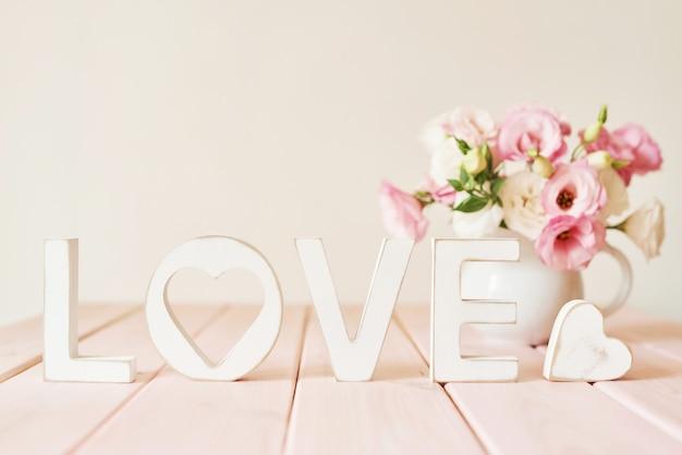 テーブルの上の花と愛という言葉 Premium写真