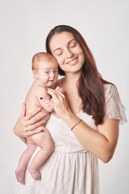 ナチュラルメイクの若い母親が赤ちゃんを腕に抱えている Premium写真