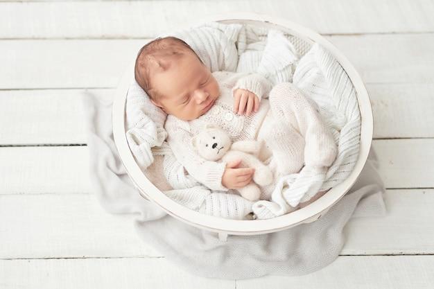 ベビーベッドで白いスーツで生まれたばかりの赤ちゃんの男の子 Premium写真